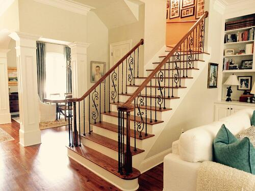 white columned living area with ornate scroll balusters going up white staircase