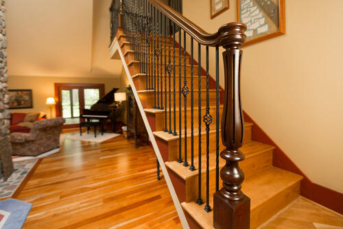 Iron Balusters and polished wooden newel on light colored wooden stairs
