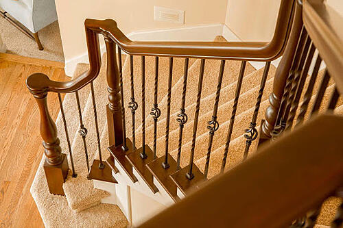 unique wood handrail with gooseneck fitting over twisted basket iron balusters on carpeted stairs