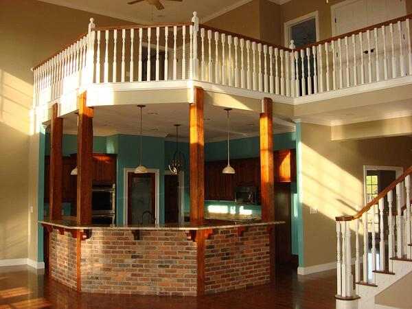 White primed balusters with wood handrail on stairs and balcony above brick kitchen